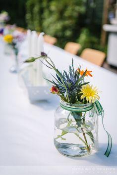 Detail van de bloemen op tafel van deze tuinbruiloft.