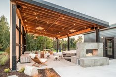The Pavilion has plenty of cozy seating, a cast concrete fireplace, and a sound system. Tagged: Outdoor, Concrete Patio, Porch, Deck, Back Yard, Shrubs, Trees, Large Patio, Porch, Deck, Hanging Lighting, and Grass. Photo 5 of 7 in Serenity Awaits at These Prefab Cabin Rentals on Vashon Island