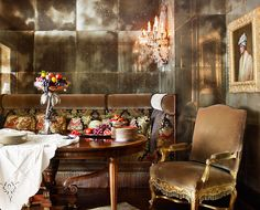 The custom banquette by Jim Couch in Old World Weavers silk velvet provides seating in the smoked-mirror dining room.