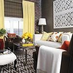 White brown zigzag rug yellow drapes exposed brick wall white lattice art white slip-covered sofa brown velvet chair white ottoman steel coffee table yellow damask pillows floral pillows red garden stool taupe gray brown grasscloth grass cloth wallpaper
