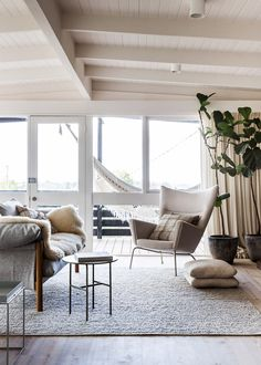 There are so many gorgeous natural elements in the home above including the Armadillo rug, furniture, sheepskin, billowy curtains and even an outdoor hammock!