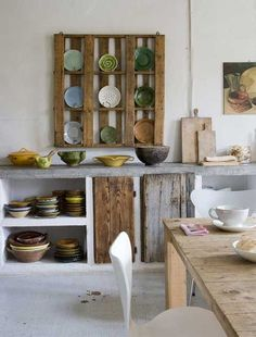 Rustic cob kitchen with reclaimed wood cupboards, shelves and table.