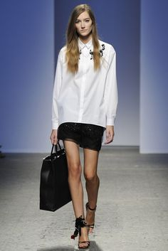 No. 21 RTW Spring 2014 - Slideshow Button-down formal shirt with barrel cuffs and black embroidery detail along collarbone over(?) black sheer dress(?) with black sparkly embroidery detail.