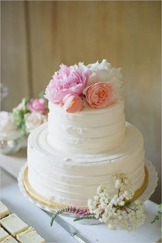 We love the white-on-white stripes on this wedding cake, topped with vibrant blooms.