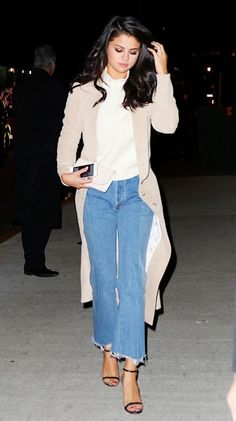 Selena Gomez wears a Victorian top, trench coat, cropped jeans, and black sandals
