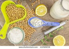 Soy mayonnaise,milk, lemon, soybeans and metallic whip, on wooden background