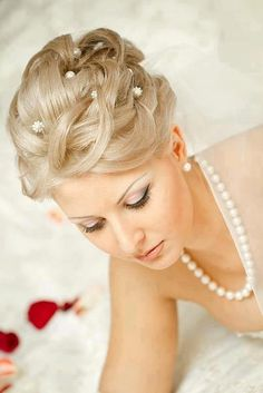 complicated bridal updo, decorated with hair pins