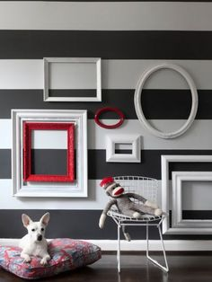 adorable!!!   Give old or unused frames a new coat of paint and a new life by grouping them on a wall!  Love the striped wall & the frames.