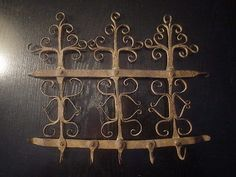 """Antique Hand Forged Wrought Iron Fancy Meat / Herb Spice Rack BlackSmith Mfg. Antique Colonial  Era black smith forged EARLY wrought iron spice / herb / meat hanging rack for use on or near the fireplace to dry & store various utilitaraian & food items. As found in very good preserved condition. No broken pieces. Made of square pinned wrought iron pieces. 5 hooks, 2 straps & 6 ornaments. Measures 11"""" across & 9"""" in height. Weighs about 1/2 pound."""