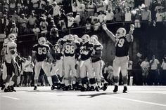 Black and white photo of a group of University of Oregon football players celebrating a success during a game played against Brigham Young University at Autzen Stadium on September 29, 1990 and won by the Ducks 32-16. Identifiable are Jeff Thomason (#83), Juan Shedrick (#24), Scott Mitchell (#98), Ngalu Kelemeni (#28) and Todd Kaanapu (#79). ©University of Oregon Libraries - Special Collections and University Archives
