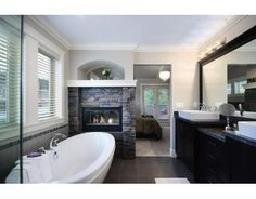 Fireplace in the bathroom with a soaker tub.