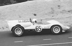 For the 1965 Bridgehampton USRRC race, Sharp's Chaparral was fitted with the same bodywork as at the previous race at Riverside. The car shows the early vestiges of the mustache spoilers first seen at the previous race. Hall's car had new rear bodywork, widened to cover the larger tires installed. Sharp's car had the older rear bodywork, and  required some cutting to avoid rubbing on the tires. Sharp finished 2nd to Hall in the typical Chaparral 1-2 finish. Stanley Rosenthall photo.