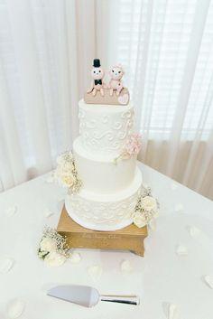 Buttercream wedding cake with fondant monkey topper and fresh flowers