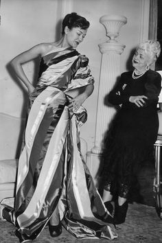 1948: Dress designer Madame Nina Ricci on the right, casting a critical eye at a mannequin whom she has draped with material to make an instant dress | Source: Getty