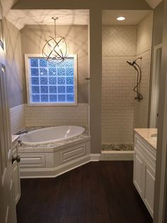 """My master bath, shower door not yet installed. Tub surround and shower floor with Botany Bay Olive Sliced Pebbles and """"Buff"""" matte subway tile. Wood-look ceramic tile floor. Delta Ashlyn Stainless faucets."""