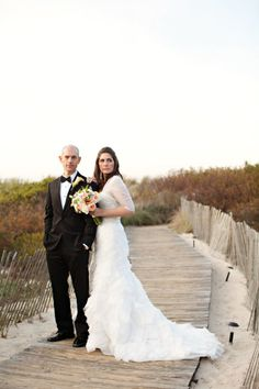 The bride and groom pose on the beach at the Ocean Edge Resort in Cape Cod.