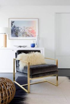 Living room corner with a gray velvet and gold armchair, a white fur throw pillow and a rattan pouf