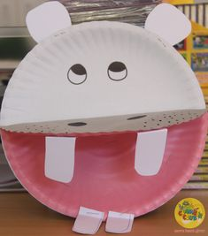 Its Zoo theme and we have created our own little hippos.  What you need: 2 paper plates (1 pink/1 white) paper permanent marker stapler  How to: Paint or purchase pink paper plates. Fold the pink paper in half and staple the bottom to a white paper plate. Cut out teeth from the white paper and staple these on either end of the pink paper plate. Draw nostrils and freckles on the back of the pink paper plate and eyes on the white paper plate!  Voila you now have a hippo!
