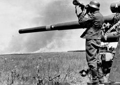 "German crew and range finder operator measures the distance to the target next to the 88-mm anti-aircraft gun Flak 18 mounted for direct fire in a field near Voronezh. On the trunk caused winning four rings. On hydro-pneumatic nakatnika caused the letter ""A"" that represents the number of the guns in the battery (in this case the first weapon)."
