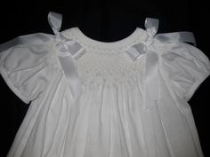 All white hand smocked bishop dress - don't have to add bows if you don't like them.  Also would be pretty with ecru smocking.