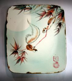 Stoneware plate painted with squirrels and maple beneath a moonlit sky. Maple represents companionship and compatibility and the moon represents heaven. By Tracie Griffith Tso of Reston, Va. #squirrel