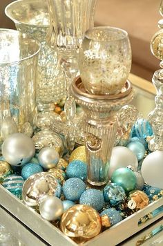Winter holiday baubles used for tablescape. Blue, gold, silver, white and teal ornaments.