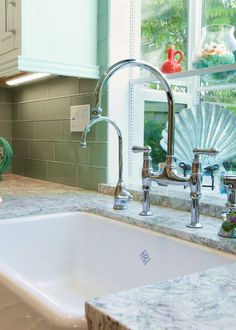 Classic features like this faucet and farmhouse sink work well with the modern accents in this Seal Beach, CA kitchen