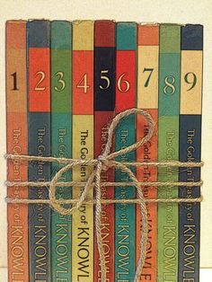 Table NumbersDecorative by beachbabyblues on Etsy, $30.00  What about using books with numbers from a series as the table numbers?