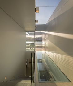 Escada de concreto com guarda corpo de vidro, piso de vidro, paredes brancas, piso de vidro e vista para praia. Cobertura Triplex no Rio de Janeiro por Arthur Casas