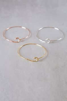 Unique fish hook clasp bracelets in gold, rose gold, and silver.
