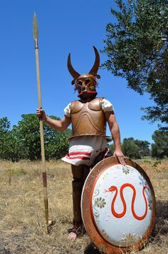 Roman Empire Clothing - A hoplite of the Archaic Period with a bell-type bronze cuirass, horned bronze Corinthian helmet, hoplite 'Argive' shield and spear. This type of armory was characteristic also for the Greeks of Sicily and Magna Graecia. Magna Graecia, Corinthian Helmet, Greek Soldier, Greek Warrior, Minoan, Iron Age, Ancient Civilizations, Ancient Greece, Roman Empire