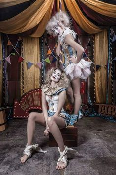 Mini vintage circus tent set up made from bunting poles and silk draping. Two pale pastel female MUA clowns standing in the middle with a roll up arrow in the background. Hire this and so many more circus props from www.propfactory.co.uk/listing