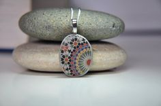 This pendant is made of genuine Mediterranean beach pebble found on one of the beaches along the Mediterranean coast of southern France, decorated with Moroccan tile detail image transfer and covered with protective layer of varnish.  As shown on the last photo, it is about 1.5/4cm long with bail included and it comes with silver plated chain.   Colors may slightly vary according to monitor settings.  As most of hand made jewelry, all the pieces that I make arent made to be waterproof but…