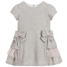Girls grey dress from Balloon Chic, made in a soft wool blend, with lightweight cotton lining. There are pretty bows with pink ribbon and diamantés on the waist, and pink tulle ruffles on each side. Kids Dress Wear, Little Girl Dresses, Girls Dresses, Baby Girl Dress Design, Baby Girl Dress Patterns, Little Girl Fashion, Kids Fashion, Kind Mode, Look