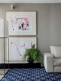 Dois quadros de mesmo tamanho ocupam o pé direito todo da sala. Projeto de David Bastos.