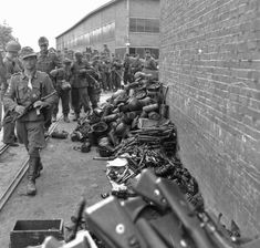 In Maarseen, the Netherlands, German soldiers surrender their arms and kit at a local factory yard supervised by British troops. The prisoner closest to the camera, looking into the lens, is carrying an MP-40 submachine gun. He wears three sleeve silver tank destruction badges awarded for destroying a tank single-handedly with a hand-held weapon. (May 10, 1945)