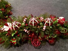 This Table Centerpiece is done on an evergreen swag can also be used on your mailbox. Its done in Red and Green mesh. It has 3 beautiful ornaments ,