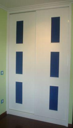 Armario empotrado con puertas correderas en blanco y rectángulos azules by Casabó interiorismo