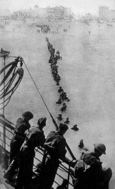 Up to their necks in water, retreating British soldiers wade through the sea because the ships couldn't get closer to Dunkirk beach, (1940)
