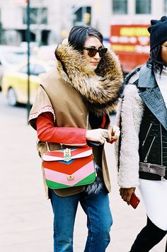 A red top is worn with a khaki vest, faux fur collar, rainbow Valentino bag, and jeans