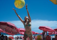 Dynamic pink umbrellas and ball over a blue sky.