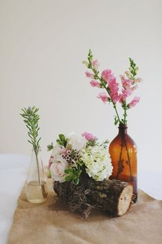 Mixed bottles and wooden logs were used with a burlap runner for a vintage look at Autumn + Taylor's reception. Florals by The Sonnet House Photo by W+E Photographie #alabamaweddings #thesonnethouse #southernweddings