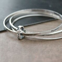 A sterling silver stacking set of three bangle are personalized with meaningful hand stamped words and family names, each with it's own unique texture and shape and held together with a petite but solid open heart charm. By 2 Sisters Handcrafted | www.2sistershandcrafted.com
