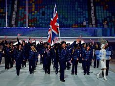 Short track speed skater Jon Eley of the Great Britain Olympic team carries his country's flag during the Opening Ceremony