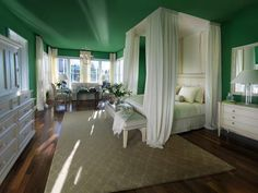 Emerald Green    Emerald green walls and ceiling provide a luxe look in this romantic master bedroom. Floor-to-ceiling white curtains and canopy curtains float through the dreamy space.