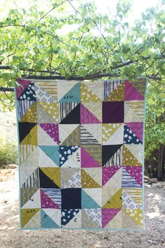 This is a simple half square triangle quilt jazzed up with fabrics from Cotton + Steels Halycon collection. These fabrics feature all sorts of motifs, including children playing, clouds, swirls, plus signs, etc. Very eclectic and fun. 54.5 x 63 100% cotton Machine wash cold/warm; tumble dry low Handmade in Santa Fe, New Mexico