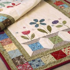 Turn these simple spool blocks of this charming table runner quilt pattern, Garden Spools, into delightful little planter boxes by adding some sweet applique flowers and leaves. Designed by Gail Pan