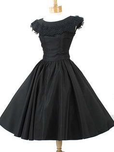 """One of a kind, authentic vintage party dress from the 1950s in crisp, rustling black taffeta fabric. Ever flattering fit and flared silhouette. Fitted, sleeveless bodice has collar embellished with gorgeous heavyweight floral lace applique. Gathered, tea length skirt is almost a full circle! Side metal zipper. Unlined. Label reads """"Petite Lady Modes"""""""