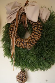 Acorn wreath within fresh greens.  Pheasant feathers incorporated into this would be so pretty.