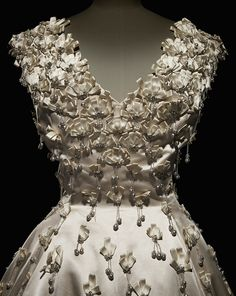 Dior 1955 Première Soirée ball gown in white acetate satin embellished with bows, paste gemstones, and gray bead pendants, worn by actress Geneviève Page, haute couture Autumn-Winter 1955, Y line. Palais Galliera, City of Paris Fashion Museum collection.